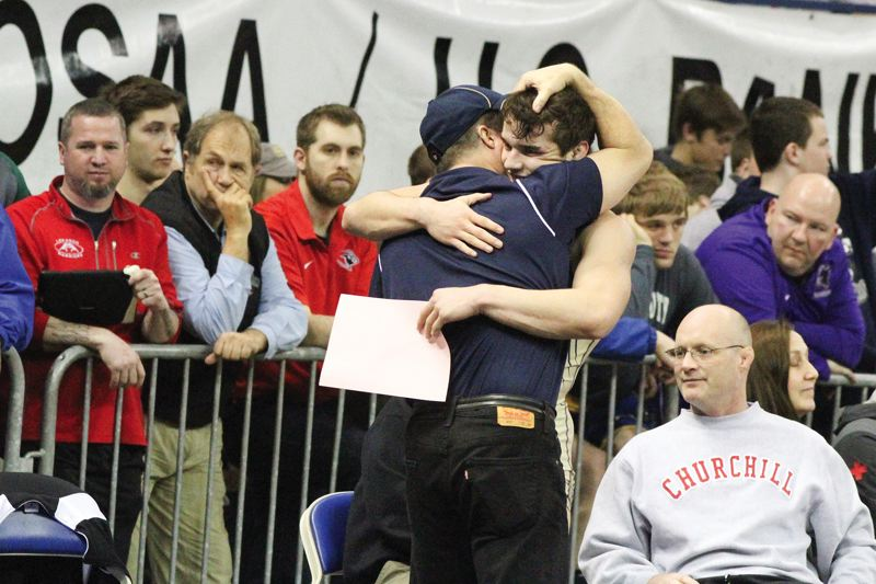 by: HILLSBORO TRIBUNE PHOTO: AMANDA MILES - Liberty senior Hunter Dehlin hugs his father, Jeff, after winning a 152-pound semifinal match at the Class 5A state tournament on Saturday.