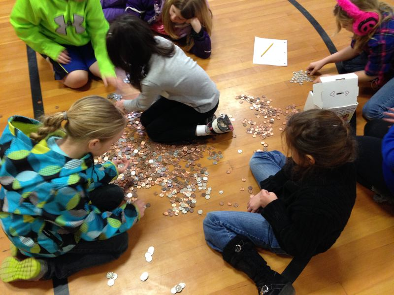 by: SUBMITTED PHOTO - Warren Elementary third-grade leadership students count change gathered during the schools Pennies for Patients fundraiser, which benefits the Leukemia and Lymphoma Society.