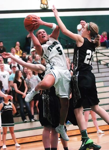 by: DAN BROOD - TWISTING FOR TWO -- Tigard senior guard Lexi Carter goes up to the basket to score two of her game-high 20 points.