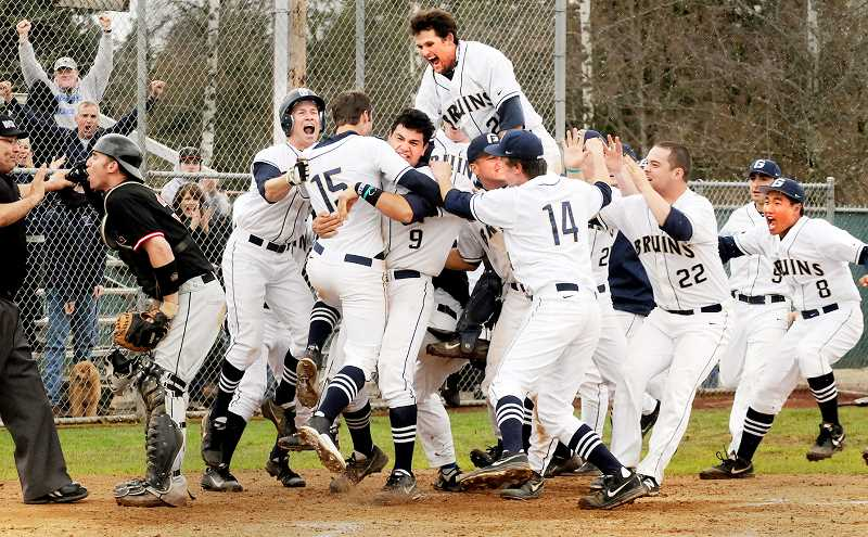 by: SETH GORDON - Mobbed - Zac Israel (15) celebrates with his teammates after scoring the winning run in the 11th inning of George Fox's 1-0 victory over Pacific Sunday.