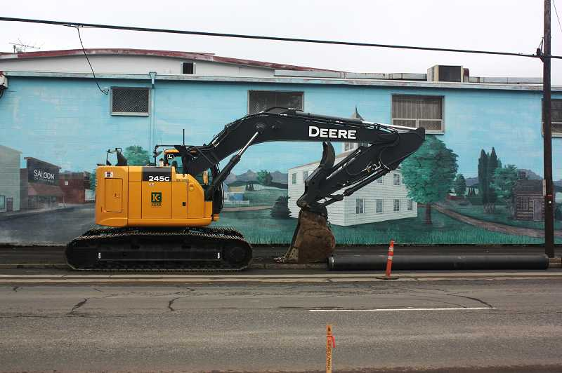 by: NEWS-TIMES PHOTO: DOUG BURKHARDT - Heavy equipment has been on the job along Baseline Street in Cornelius in recent weeks, including, as seen here, in front of the colorful mural on the old Hanks Thrifway building.