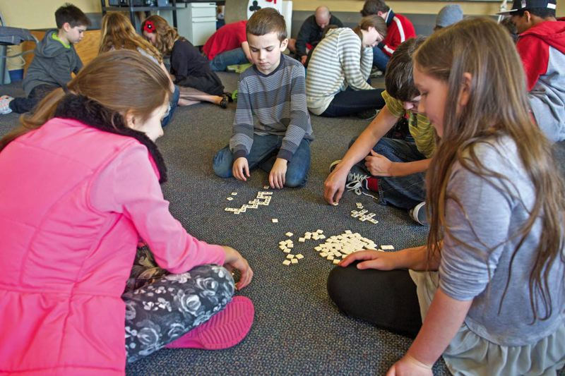 by: TRIBUNE PHOTO: JAIME VALDEZ - Gabby Calvi, 10, left, Will Mueller, 10, Joe Finley ,13, and Autumn Straus, 10, play Bananagrams during a class at Village Home Education Resource Center in Beaverton. The home-schoolers are learning the roots of words as part of the centers language and spelling classes.