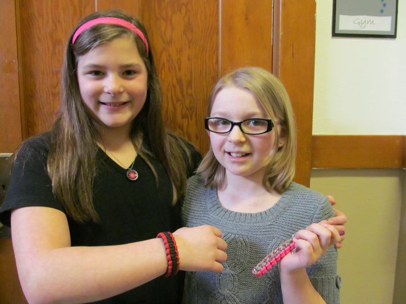 by: PHOTO BY ELLEN SPITALERI - Joelle Robeson, left, models a bracelet, while Natalie Ramsey holds a keychain. The girls hope to sell the items and donate the money to charity.