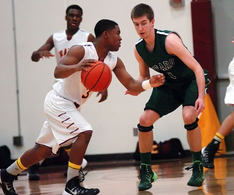 by: DAN BROOD - TOUGH DEFENSE -- Tigard senior Nick Kaelin (right), the Pacific Conference Defensive Player of the Year, keeps a close eye on Central Catholic junior guard Deante Strickland.