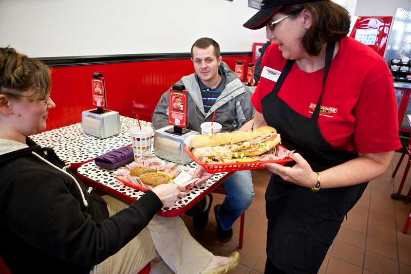 by: TIMES PHOTO: JAIME VALDEZ - Firehouse Subs employee Cathy Wells serves sandwiches to Brandon and Renata Lasich of Scappoose at the new location at Cedar Hills Crossing. The Lasiches are huge fans of Firehouse Subs and once made a special trip to Las Vegas for their favorite sandwiches.