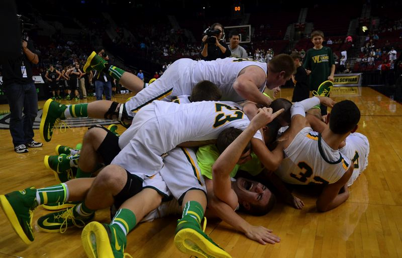 by: VERN UYETAKE - The West Linn boys basketball team mobs each other on the floor of the Moda Center after winning it second straight state championship.