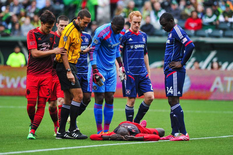 by: COURTESY OF JOHN LARIVIERE - (From left), Portland Timbers forward Maximiliano Urruti, referee Marcos de Oliveira, Chicago Fire goalkeeper Sean Johnson, Chicago midfielder Jeff Larentowicz and Fire defender Jhon Kennedy Hurtado check the condition of Timbers defender Mamadou 'Futty' Danso after a collision with goalkeeper Johnson.