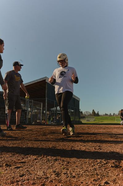 by: JOHN WILLIAM HOWARD - Lion senior Kali Moore trots into home plate during practice last week. St. Helens has been putting more of a focus than usual on scoring runs, an issue for the team last season.