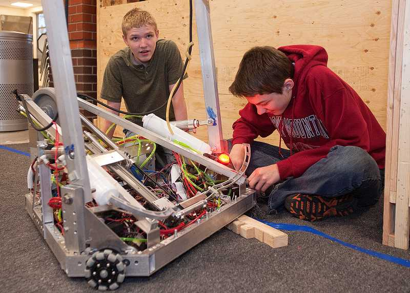 by: SPOKESMAN PHOTO: JOSH KULLA - Wilsonville High robotics team members Jacob Tiederman, left, and Tristan Briggler assemble the student-designed and -built mobile pit where the team works on its robot during competition. The entire pit breaks down and folds up into a large box roughly 6 feet long and 4 feet tall. It sits on casters and is readily movable despite weighing roughly 800 pounds.