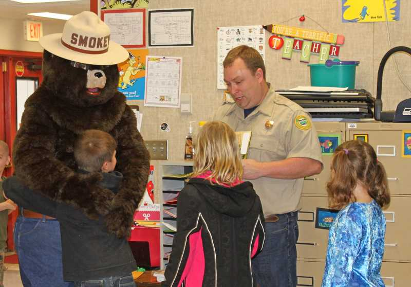 by: LIZ WELLE-OEDELL - Clarkes Elementary Students line up to give Smokey the Bear hugs and high fives.