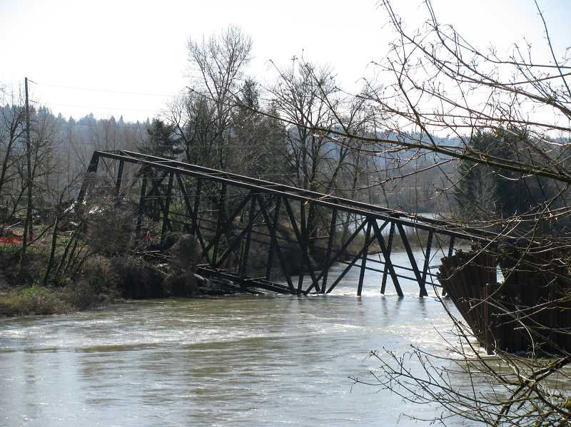 by: PHOTO COURTESY OF KOIN TV - After showing signs of failure, crews dragged the old trolley bridge truss out of the Clackamas River and broke it up into pieces on land.