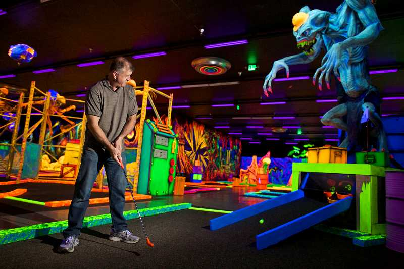 by: TIMES PHOTO: JAIME VALDEZ - Glowing Greens owner Ray Latocki putts at the 18th hole as 'Larry' the alien hovers above. Latocki's grandson, Remi, provides his voice to the alien.