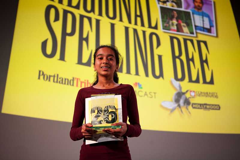 by: TIMES PHOTO: JAIME VALDEZ - Divya Amirtharaj displays her award for winning the 2014 Portland Tribune/Comcast Regional Spelling Bee on Saturday at the Hollywood Theatre in Northeast Portland. It was the second consecutive year she won the regional bee.