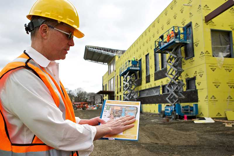 by: TIMES PHOTO: JAIME VALDEZ - Jeff Houghtalling, VillaSport Athletic Club and Spa's membership director, shows a map of the layout of the new club across from Nike World Headquarters at Southwest Jenkins Road and Murray Boulevard.