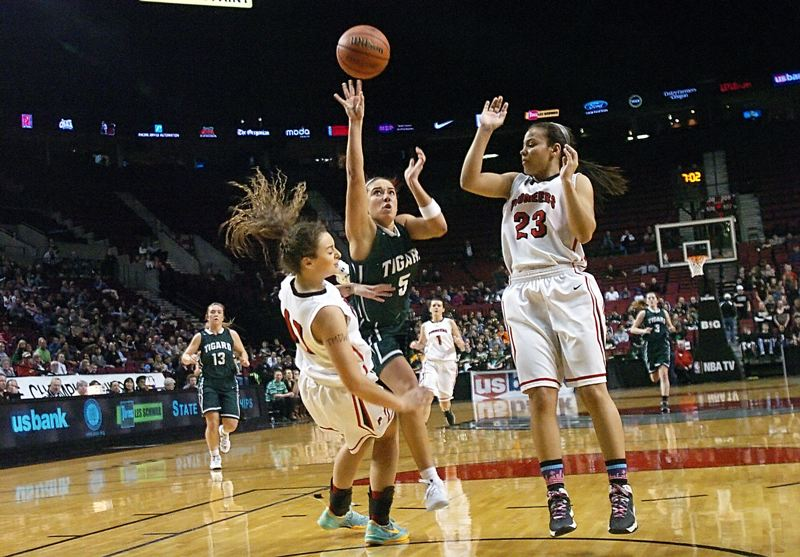 by: DAN BROOD - IN BETWEEN -- Tigard High School senior guard Lexi Carter (5) drives hard to the hoop between Oregon City's Taylor Shaw (left) and Toria Bradford during last week's Class 6A state tournament quarterfinal game.