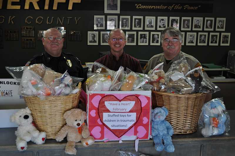 by: CONTRIBUTED PHOTO - Prineville Police Captain Mike Boyd (LEFT), Reverend Mike Wilson (CENTER), and Sheriff Jim Hensley (RIGHT) display the teddy bears collected during a teddy bear drive.