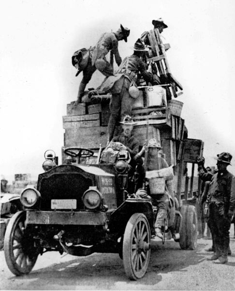by: OREGON NATIONAL GUARD - Oregon National Guard troops move their camp along the Mexican border in an pre-1916 truck with right-hand steering, a remnant of the horse-drawn wagon days.