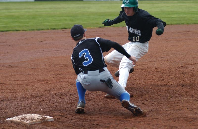 by: ESTACADA NEWS: PARKER LEE - Estacadas Jordan McDaniel works to sidestep Woodburns third baseman during last weeks 3-2 home win.