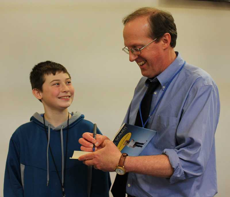 by: SPOKESMAN PHOTO: KATE HOOTS - Author Gary Schmidt autographs a copy of his book 'OK for Now' for seventh-grader Corsy Smith.