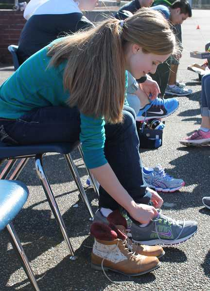 by: SPOKESMAN PHOTO: KATE HOOTS - Sophomore Jaclyn Marston tries on shoes provided by Portland Running Company March 12.