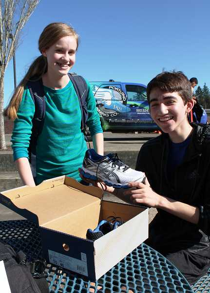 by: SPOKESMAN PHOTO: KATE HOOTS - Nick Crosby, a sophomore, shows off the shoes he received as part of his membership in Willie Fit, the WHS running club.