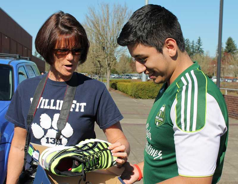 by: SPOKESMAN PHOTO: KATE HOOTS - Joe Vanny, a senior, shows his new shoes to Willie Fit adviser Lyndi Tucker.