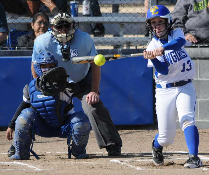 by: LON AUSTIN/CENTRAL OREGONIAN - Aspen Christiansen rips a single during the first inning of gane one of the Cowgirls' doubleheader  against the Madras White Buffalos. The Cowgirls won both games of the doubleheader, played on Saturday in Madras.