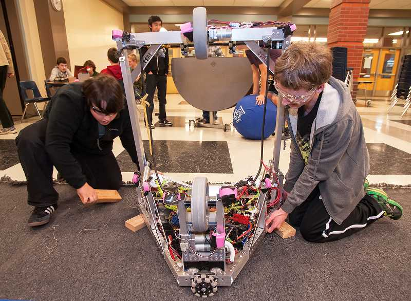 by: PAMPLIN MEDIA GROUP: JOSH KULLA - Adrian Shotola-Hardt, left, and Kjel Petterson-Willey fine-tune FIRST Team 1425's robot ahead of the regional competition at Wilsonville High School March 21 and 22.