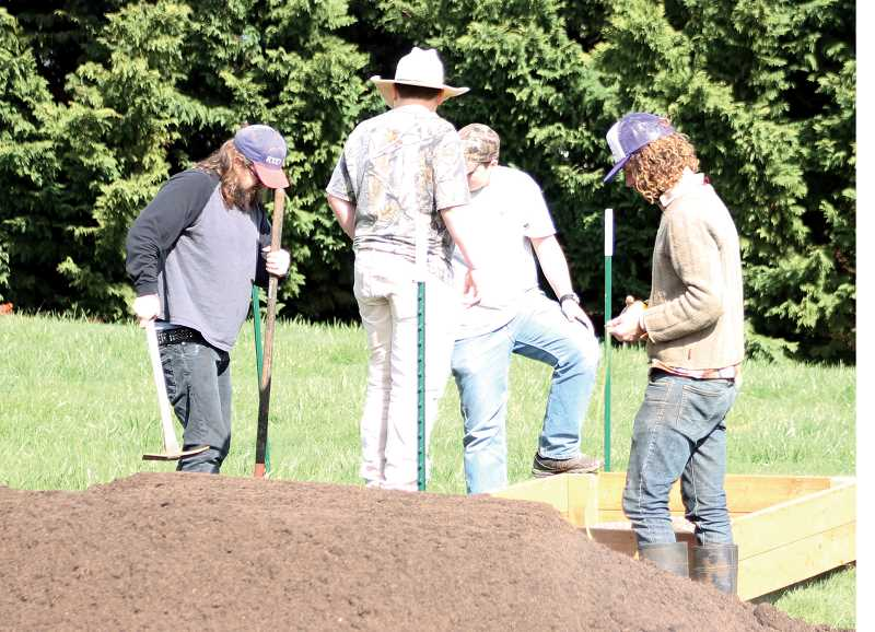 by: CORY MIMMS - Left to right, Matt Brown, Christopher Boss, Aaron Boss, and Daniel Whipple put the beds in place.