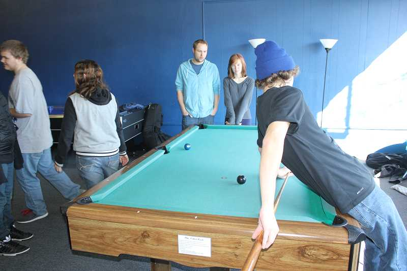 by: SUSAN MATHENY/MADRAS PIONEER - Zac Caldwell, back center, talks with students at the City Life rec room in Madras.