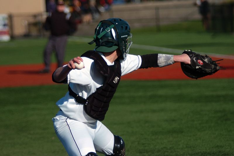 by: DAN BROOD - MAKING THE PLAY -- Tigard junior catcher Jared Gogal looks to fire the ball to first base after fielding a bunt in Saturday's game with Central Catholic. In addition to getting the out on this play, Gogal also threw out a Ram runner in a stolen-base attempt.