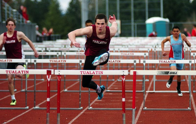 by: DAN BROOD - WINNING FORM -- Tualatin High School senior Robbie Ellis (center) is on his way to victory in the 110-meter high hurdles race at last week's season-opening track meet with Centennial. Ellis also triumphed in the 300 intermediate hurdles.
