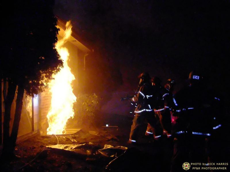by: DICK HARRIS/PF&R - Fierfighters battle flames at early Thursday house fire.
