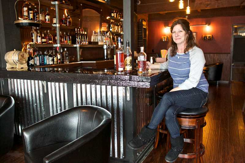 by: TIMES PHOTO: JAIME VALDEZ - Carla McQuade, co-owner of Bootlegger's Whiskey Bar, is ready to open the doors of the Prohibition-style bar on Southwest Broadway Street in downtown Beaverton.