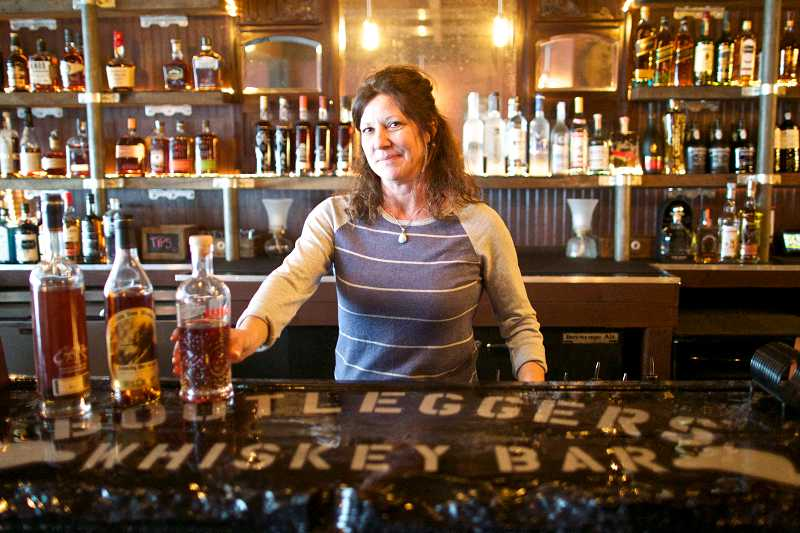 by: TIMES PHOTO: JAIME VALDEZ - Carla McQuade, co-owner of Bootlegger's Whiskey Bar, shows off the bar at the old town Beaverton watering hole she and her partners will open in early April. Bootlegger's will serve specialty cocktails made with from a broad selection of high-end whiskeys, scotches and other spirits.