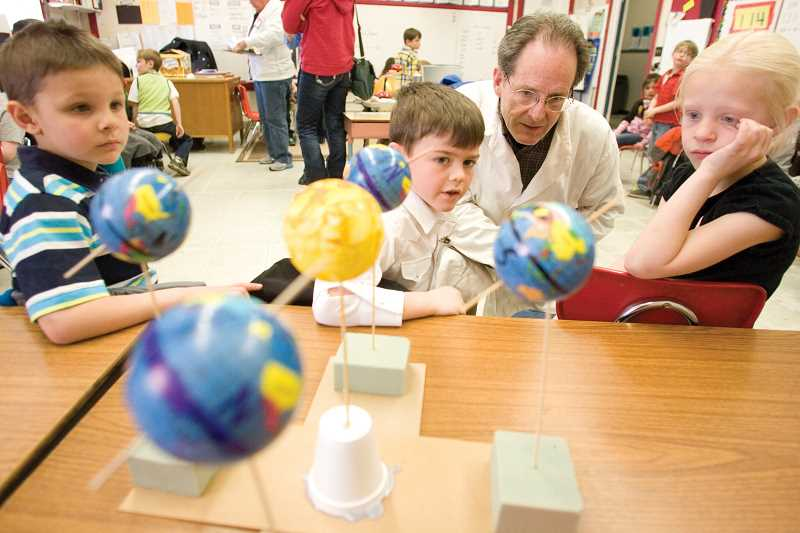 by: KEVIN SPERL - Dr. Luminous, aka Allen Beekman, visits with first-grader Tanner Joyce to learn about the earth's position to the sun and the student's 'reasons for the seasons.'