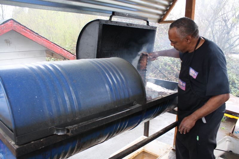 by: SPOTLIGHT PHOTO: ROBIN JOHNSON - Ron Washington, owner of Ron Rico's BBQ To Go, flips ribs in his steel-drum grill Wednesday, March 26.