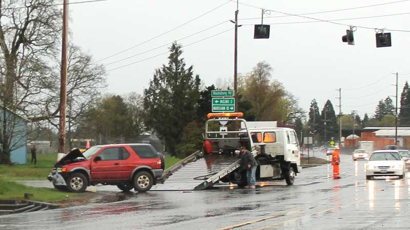 by: CORY MIMMS - A tow truck driver clears one of the vehicles involved in the crash.