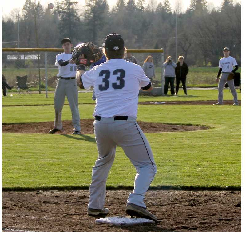 by: LACEY MCGRAW - Pitcher Jordan Syphard throws to first baseman Cooper Nofziger in the Cougars' opening game against Gervais.