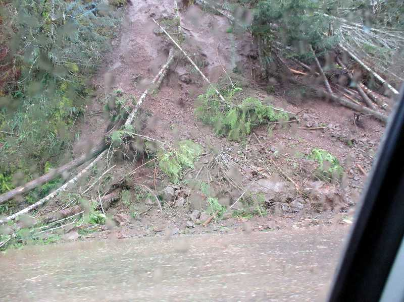 by: PHOTOS COURTESY OF AKEKE THOMPSON - It was still raining as Highway 6 finally opened after a landslide and 12-year-old Akeke Thompson shot a photo through his car window as they passed these boulders on the roadway.