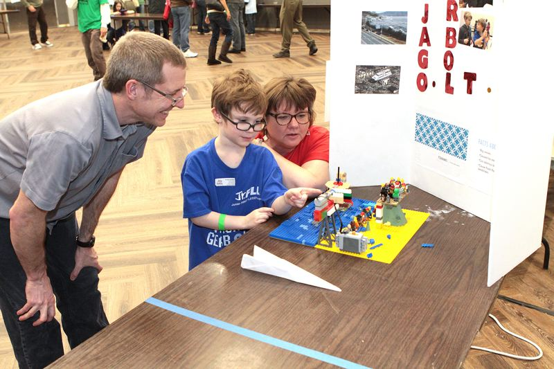 by: DAVID F. ASHTON - Dad Dan Bryan watches with pride as his kindergartener son, Max Bryan, demonstrates the effect of a tsunami to Cathy Swider of the Oregon Robotics Tournament & Outreach Program.