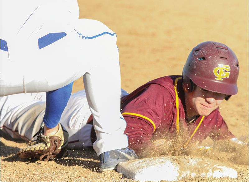 by: NEWS-TIMES PHOTO: AMANDA MILES - Forest Grove sophomore C.J. Friedman slides safely back into first base on a pickoff attempt last Friday in a nonleague baseball game against Aloha. The Vikings won the game, 4-1.