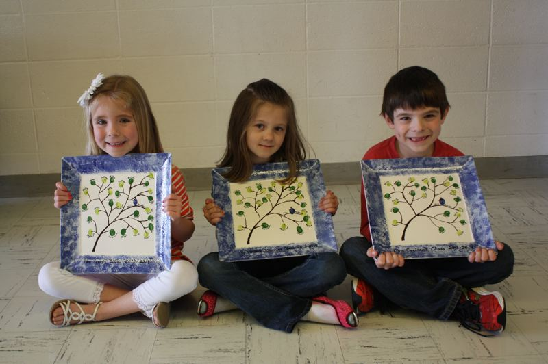 Grant Watts Elementary School Kindergarten students hold finger-print plates. The students' artwork will be auctioned off at the event, as well as many other items. Left to right: Kennady Hoag, Kayleigh Fraser and Paxton Squires.