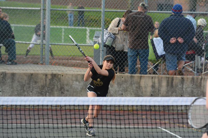by: JOHN WILLIAM HOWARD - St. Helens senior Madison Kaplan returns a serve during the Lions' match against Sandy on April 2. The tennis courts have been in poor repair for 'six or seven years' according to the boosters, and are scheduled to be replaced.