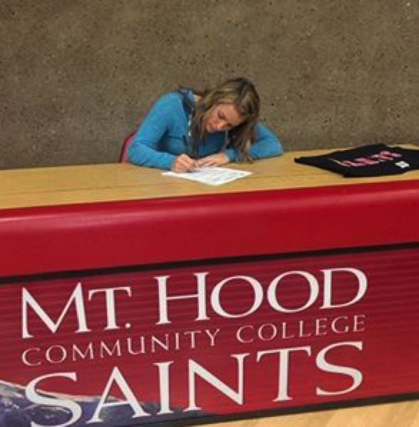 by: SUBMITTED PHOTO - Scappoose senior Lacey Updike signs her letters of intent to play basketball and softball at Mt. Hood Community College.