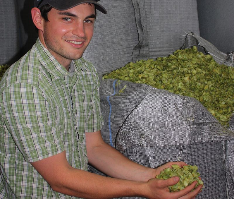 by: HILLSBORO TRIBUNE PHOTO: DOUG BURKHARDT - Blake Crosby, whose family owns a hop farm about 20 miles north of Salem, shows off some of the hops grown on his farm, which primarily go to craft breweries in Oregon. About one pound of hops produces one barrel of beer.