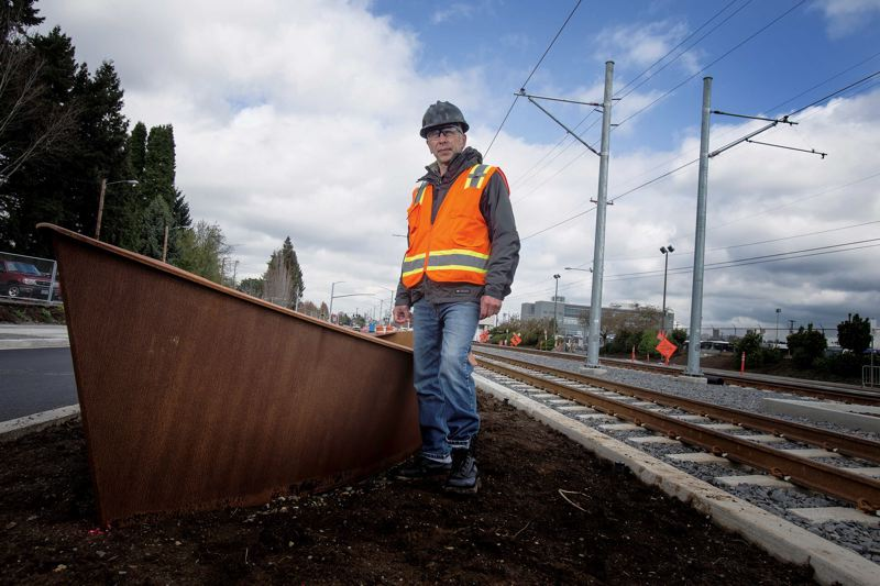 by: TRIBUNE PHOTO: JONATHAN HOUSE - Conceptual artist and sculptor Bill Will with one of his one-ton metal boats that sit along the new Portland-to-Milwaukie light-rail line in Southeast Portland.