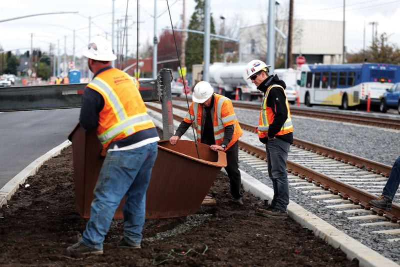 by: TRIBUNE PHOTO: JONATHAN HOUSE - TriMet crews place one of the metal boat sculptures near light-rail tracks on Southeast 17th Avenue.