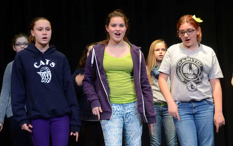 by: PAMPLIN MEDIA GROUP: VERN UYETAKE - From left, foreground, Dana Knote, Josie Cammack and Sydney Smit rehease with the cast of Footloose, the 2014 middle school musical.