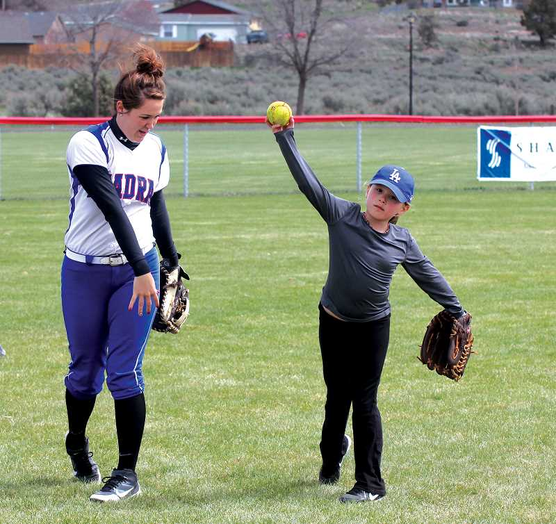 by: JEFF WILSON/THE PIONEER - Madras outfielder Keeley Brown works with Hope King during Saturday's fastpitch clinic.